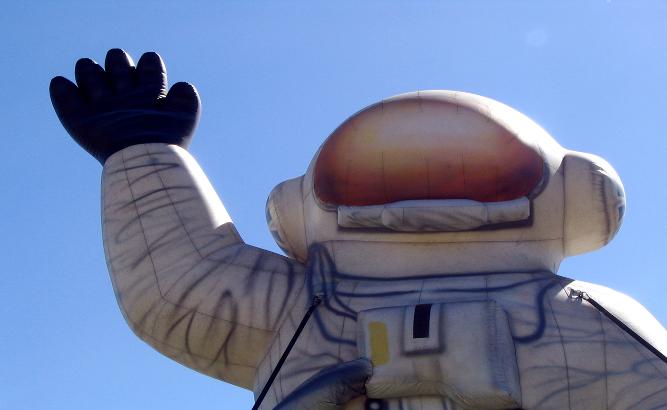 宇宙服をきて右手を挙げてる様子