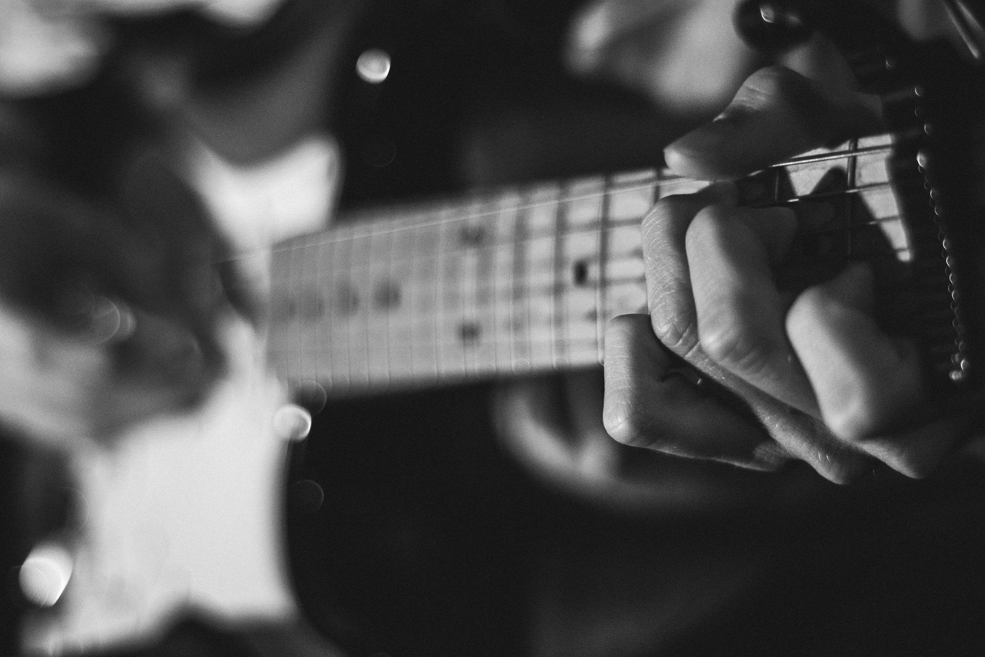 ギターの引き方を教えてる男